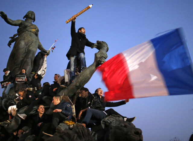 A man holds a giant pencil as he takes part in a Hundreds of thousands of French citizens solidarity march (Marche Republicaine) in the streets of Paris